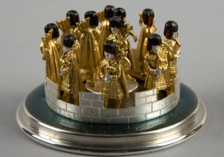 Small model of eleven bag pipe players at the top of a turret, in silver gold and black
