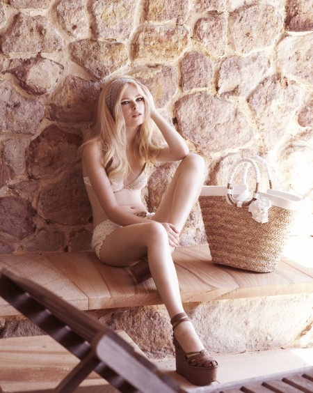 Woman styled in a 1960s look sitting on seat against stone wall in white bikini with handbag