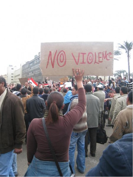"""Photograph of protest with a woman holding up sign with the text reading """" No Violence"""""""