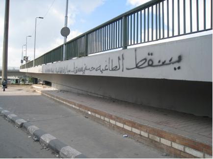 Spray painted bridge in Arabic text