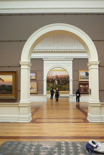 Interior view of a museum looking through classical archways