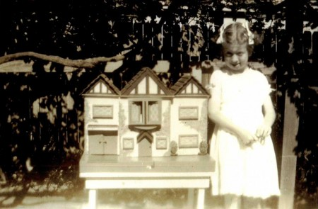 Black and white image Janet Vanderfield aged 7 in 1942 with her doll's house