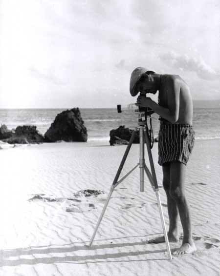 Photograph of Helmut Newton standing on the beach taking a photograph by Janice Wakely taken at Lorne, near Melbourne