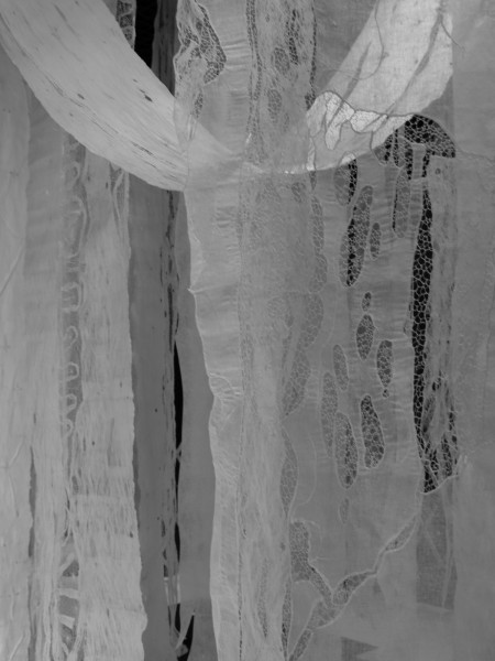 Large sheets of lace hanging in a black and white photograph