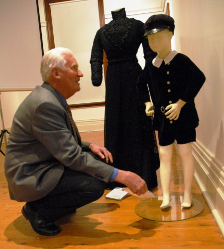 Norman Myott grandson of Hilda Smith whose black dress (1908-1912) is on display behind the boys outfit 'Boys black velveteen dress, Griffith Pioneer Museum
