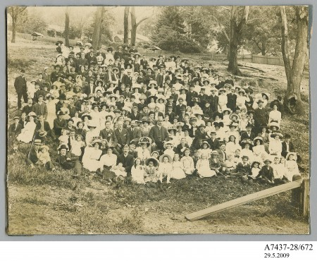 Black and white photograph taken large group of 100 people in the early 1900's