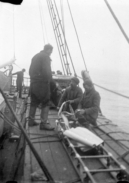 Black and white photograph of men working on a sledge harness on the 'Aurora'