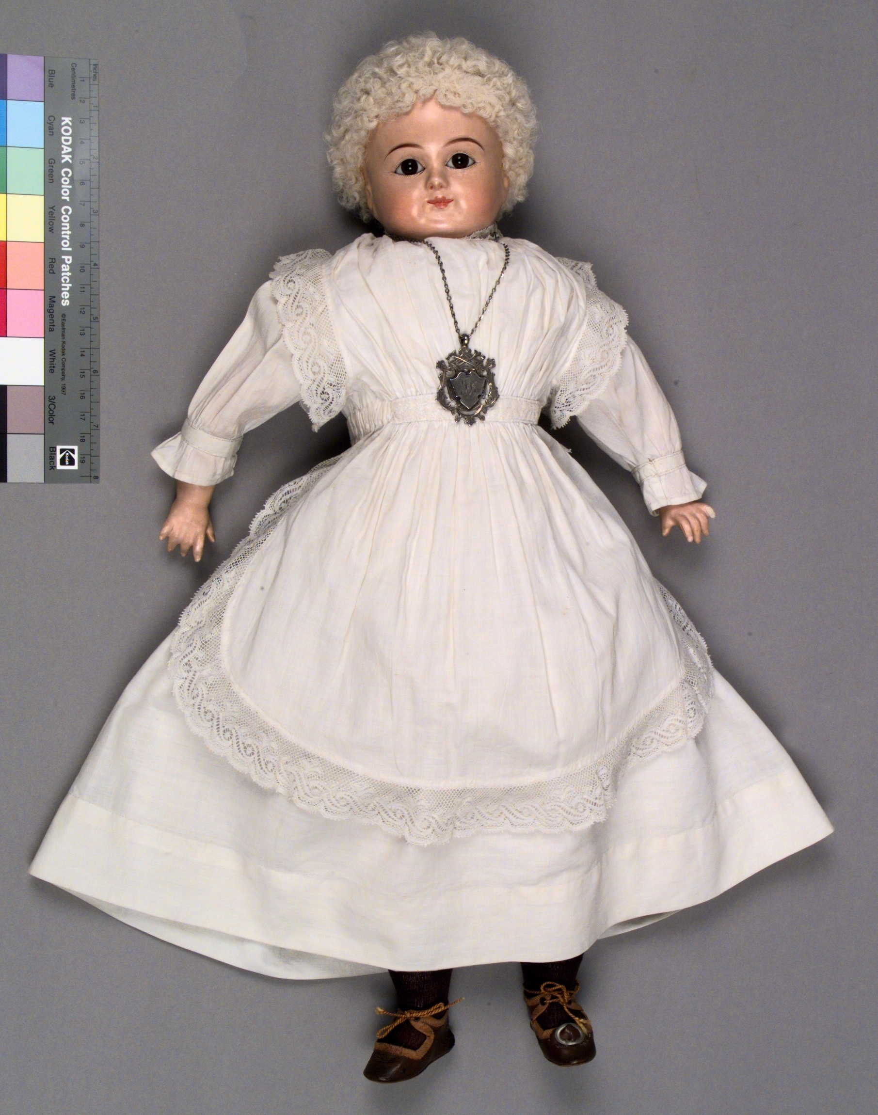 Florence Breaden's doll wearing a long white lace trimmed dress sewn by her as an 8-year-old
