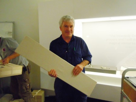 A man dressed in overalls holds a rectangular board and smiles at the camera. Behind him is an empty display wall for an exhibition installation in progress and another man working at the edge of the picture.