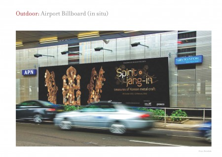 Two blurry cars drive past a billboard on the side of a car park. The billboard is black with 3 intricate gold objects on the left. On the right the billboard reads 'Spirit of jang-in/ treasures of Korean metal craft'.