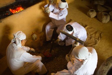 Four men hammering the baduk