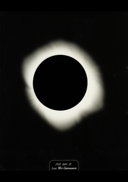 A black and white photograph of solar eclipse, seen as a black circle surrounded by an irregular a halo of light, on a black background. At the bottom is a small plaque which reads, 1922 September 21, Lick 40 feet Coronagraph.
