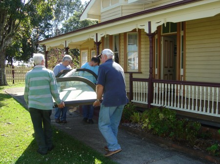 Carrying the top of the display case into Crawford House Museum