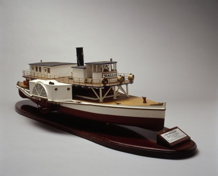 Model of a paddle steamer painted in red and white. The steamer has a wide lower deck with an upper deck with a small cabin for the helm as well as an exhaust chimney. The model is mounted on a wooden pedestal with a plaque at the bow.