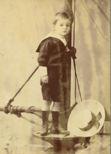 Sepia photograph studio portrait of box kite inventor, Lawrence Hargrave's son, Geoffrey, in a sailor suit