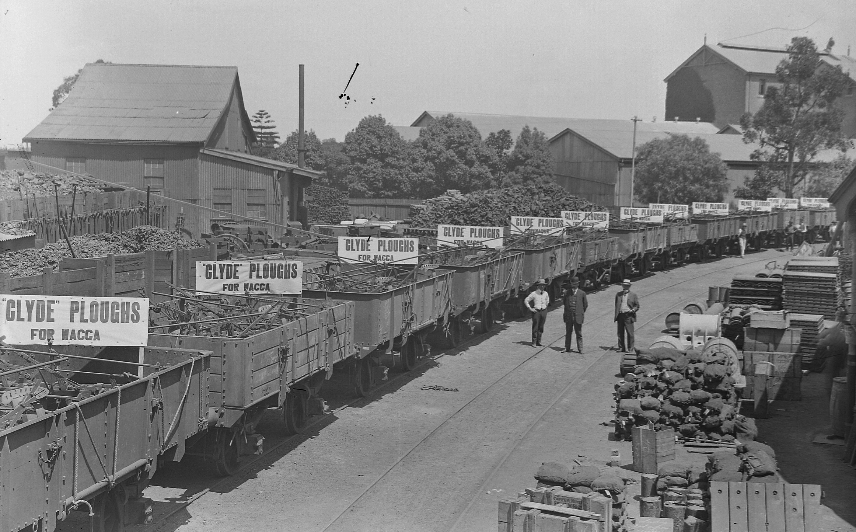 Black and white photograph of three men standing in a factory yard beside a long line of train wagons loaded with ploughs. The wagons have signs which read Clyde Ploughs for WACCA.