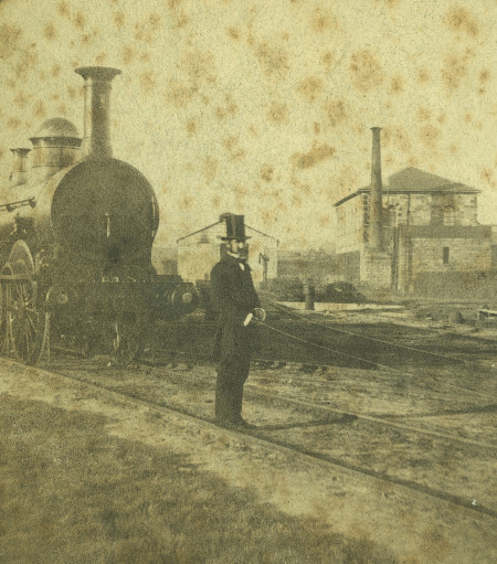Sepia photograph of a man dressed in a top hat and frock coat standing before a steam engine on train tracks. There are sheds and buildings in the background and some age or water damage to the photograph.