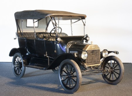 A black 1910s-era car with an open-top carriage and a convertible roof-covering which attaches to the front windscreen and the rear seat. The wheels of the car are very narrow yet have a wide diameter giving the car a high-set seating carriage.