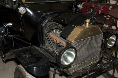 A closeup of the engine of the car from the first image with the hood lifted. The front grill is inscribed with the brand name Ford. On either side are two round headlights. The interior of the engine has black wiring and an orange pipe or tube.