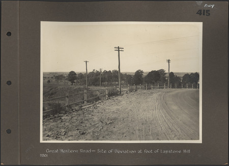 A black and white photograph stuck to a scrapbook page showing a dirt road lined with a fence and telegraph poles. The photo is labelled 'Great Western Road- site of deviation at foot of Lapstone Hill'. The left side of the page has binder holes.