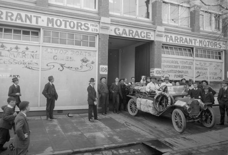 A black and white photograph of a family of four and their dog sitting in the same type of car depicted in the first image. The car's roof is removed and it is parked in front of a building labelled Tarrant Motors Garage surrounded by a small crowd.