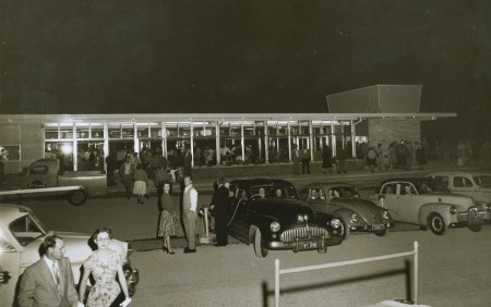 Black and white photograph of four cars parked in a row in front of a building. Speakers on a wire have been threaded through the driver's front windows. There are also people standing around in semi-formal attire.