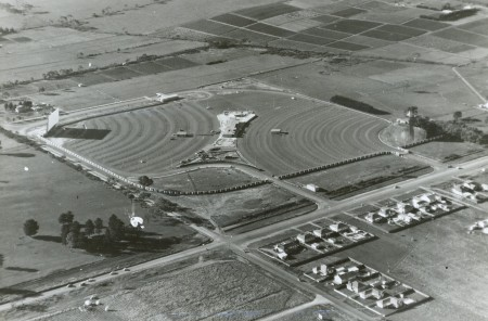 Black and white aerial photograph showing a square field used for a twin drive-in. The drive-ins each occupy a triangular half of the field. It is surrounded by other empty fields except for the bottom right where there are a series of houses.