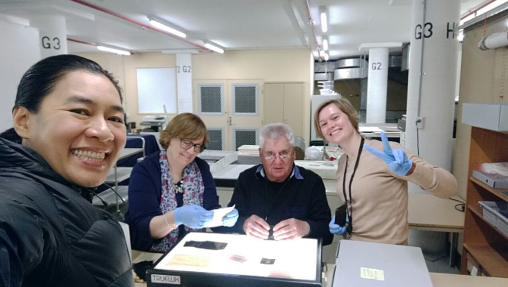 Photograph of Curator & Volunteers with negatives and envelopes