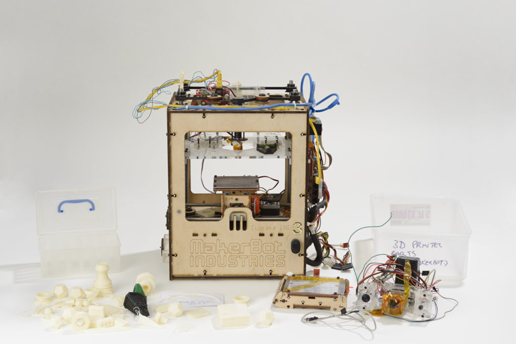 3D printer constructed out of plywood, surrounded by printed objects.