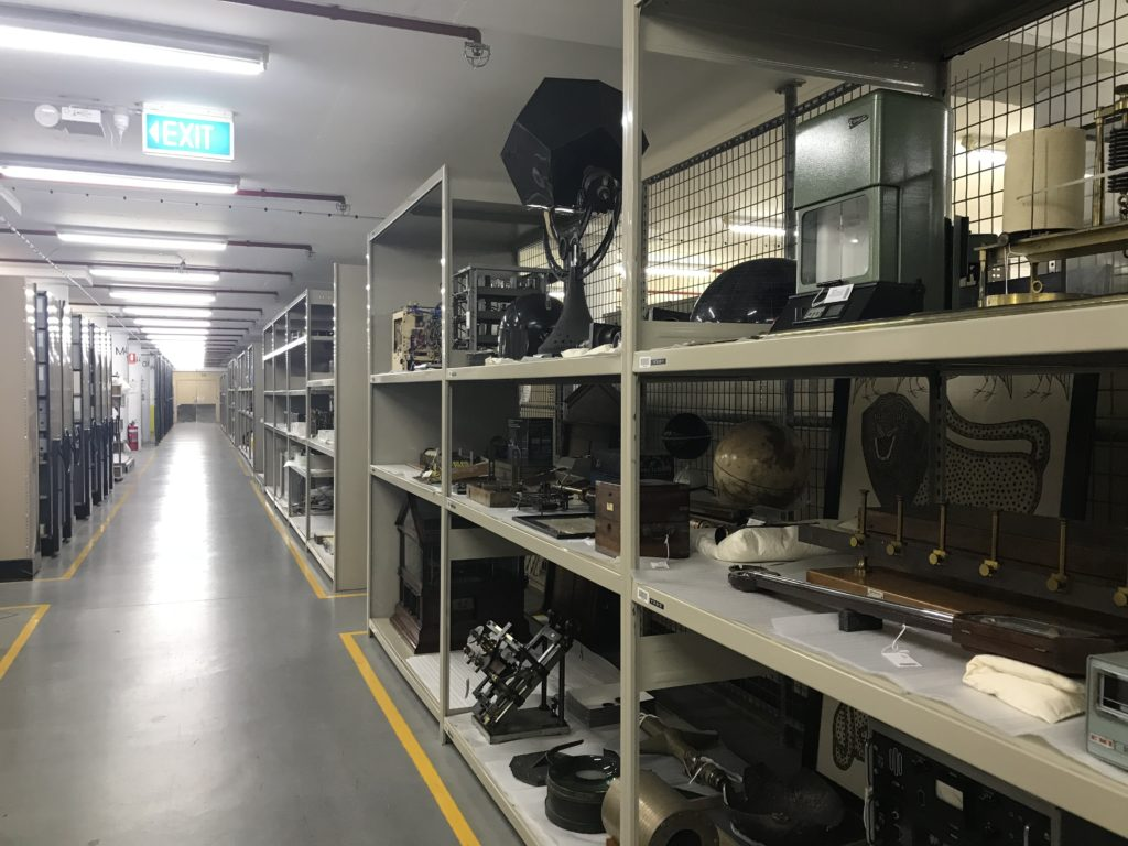 A long corridor with shelving units running down each side. Each unit has lots of objects stored on each shelf.
