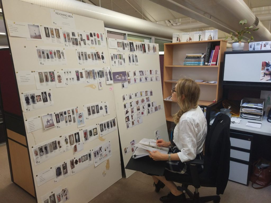 Assistant Curator Alysha Buss reviewing a folder of object research files with the brainstorm pin boards