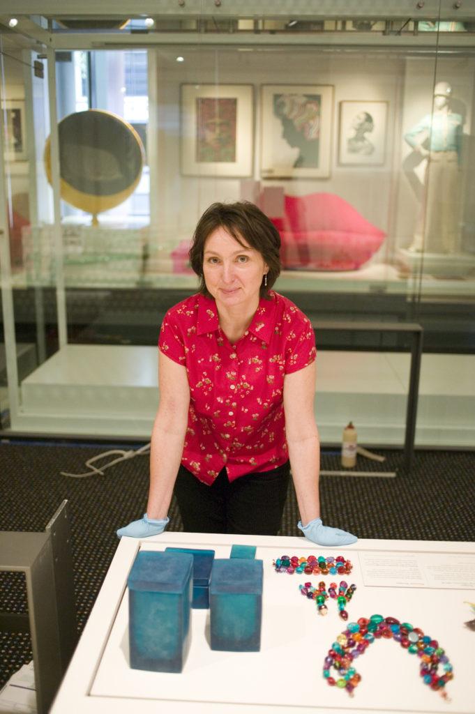Curator Eva Czernis-Ryl installing 'Dinosaur Designs' jewellery