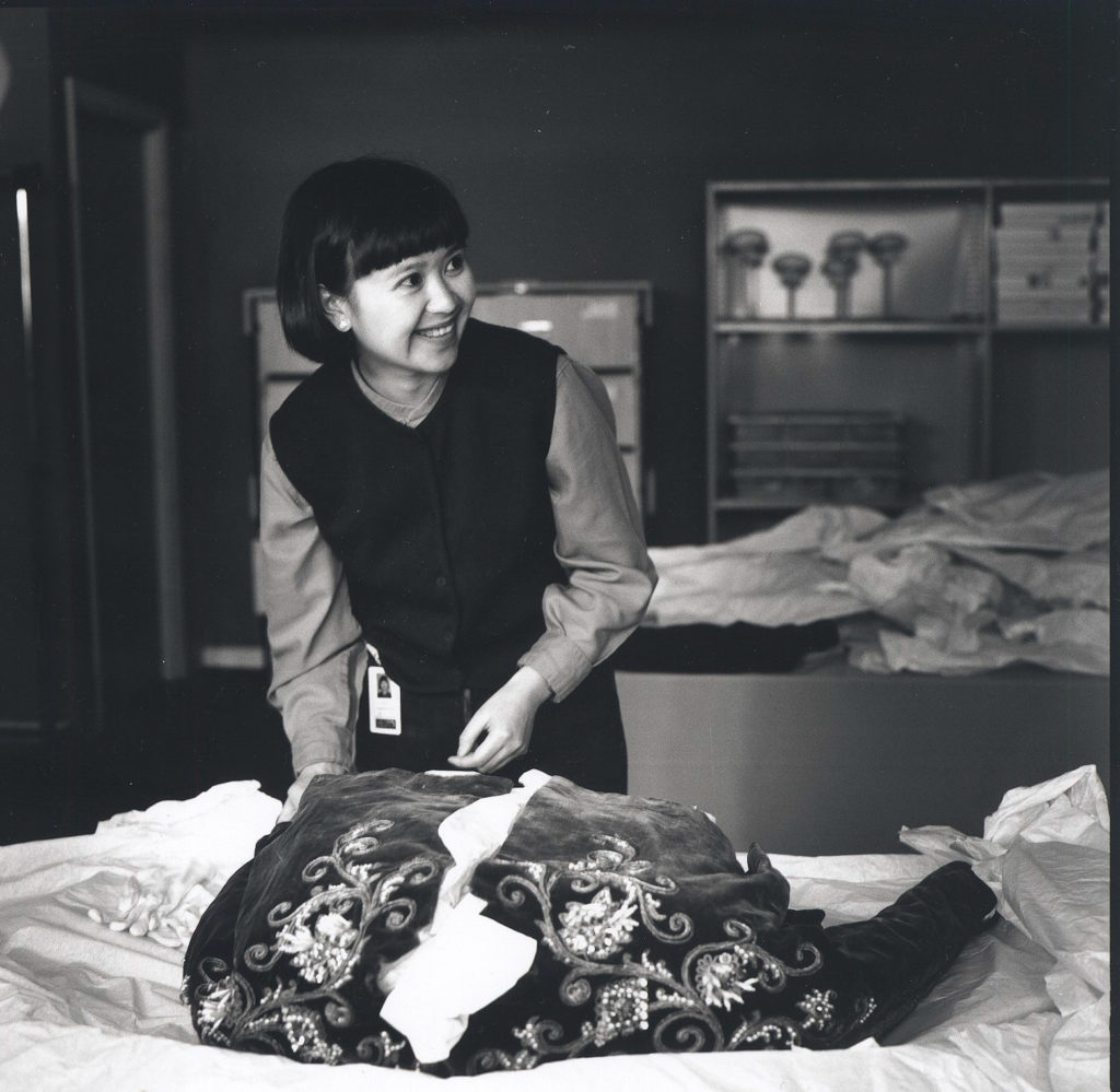 Photograph of Conservator Suzanne Chee working on Dior velvet jacket