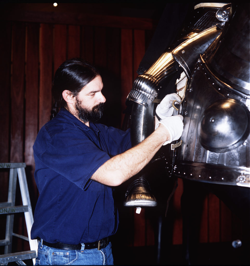 Registrar Cary Ward works on a suit of armour