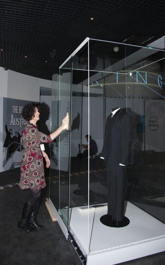 Registrar Katrina Hogan cleaning the showcase holding a suit worn by John Lennon