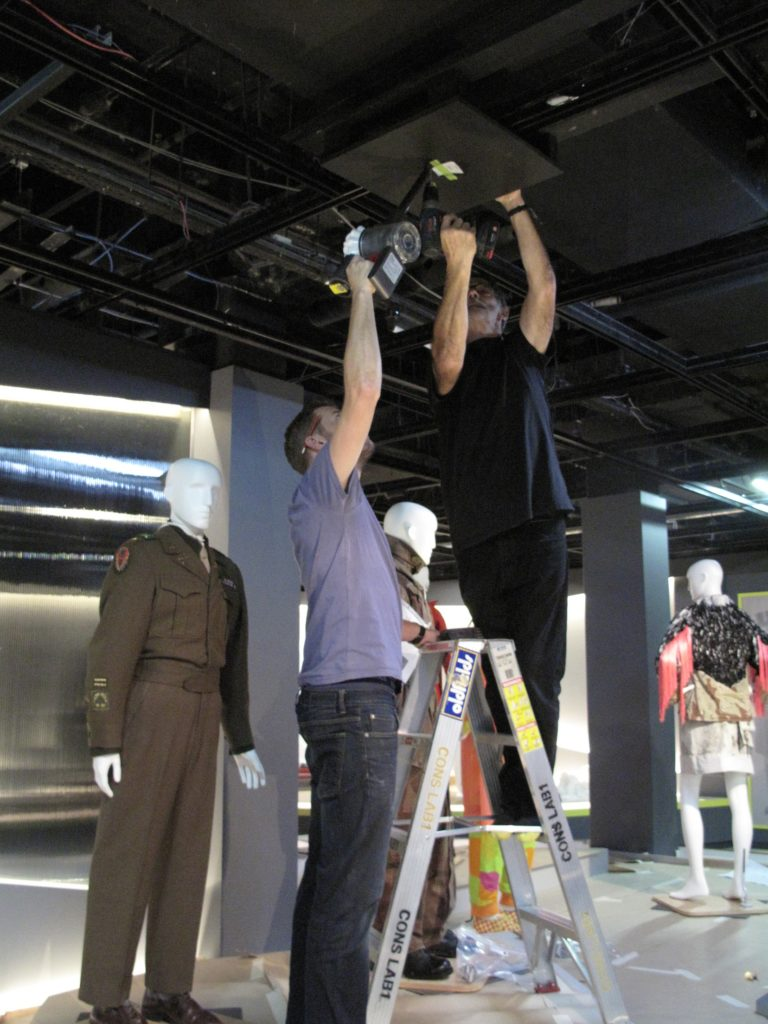 Scott Winston, Assistant Registrar and Carey Ward, Registrar, fixing wooden boards to the ceiling from which the jackets were suspended with four lengths of steel wire