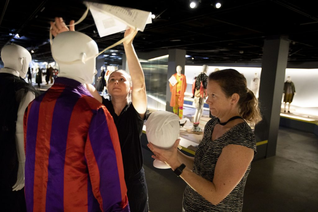 Sarah Heenan, Collections Officer and Bronwyn McKenzie, Registrar (MAAS), place the wig for the Smoking suit