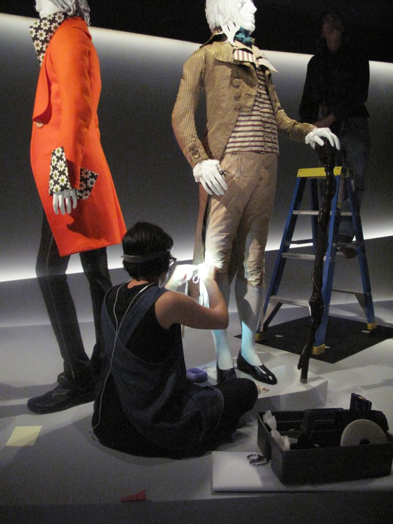Rachel Tu, Collections Manager (LACMA) tying the reproduction silk bows on the breeches of the Incroyable ensemble, 1790