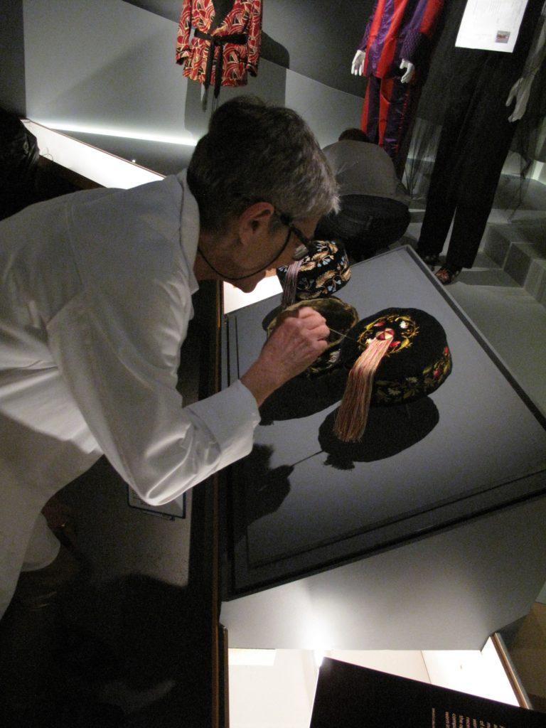 Kaye Spilker, Curator, straightening the silk tassels of the Smoking caps
