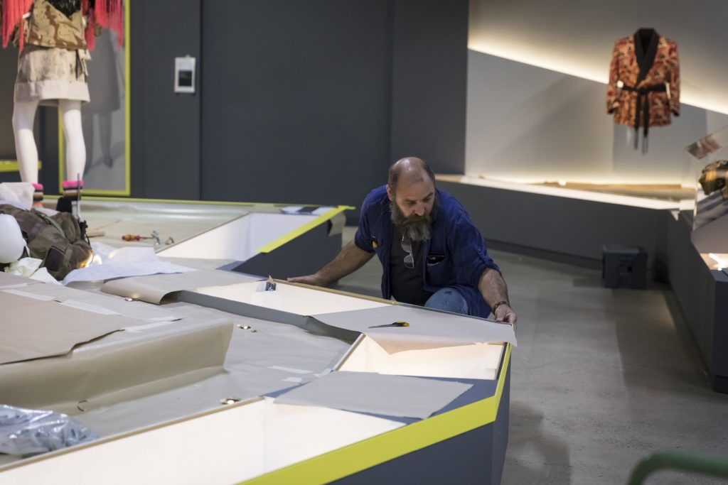 Gavin Lewis, Workshop Preparator (MAAS), fixing the coloured strips which signalled the five thematic groupings of the exhibition.
