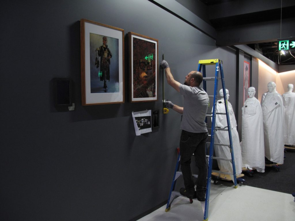 Garth Knight (freelance installer) installing photographs, posters and illustrations