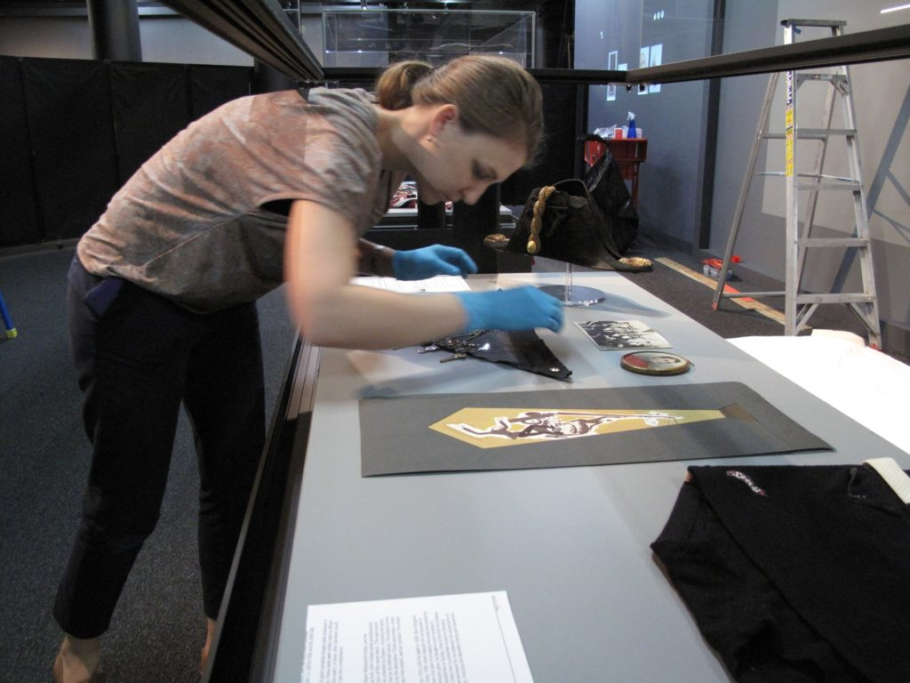 Vanessa Thorne, Assistant Curator (MAAS) installing objects in Australian Men's Style