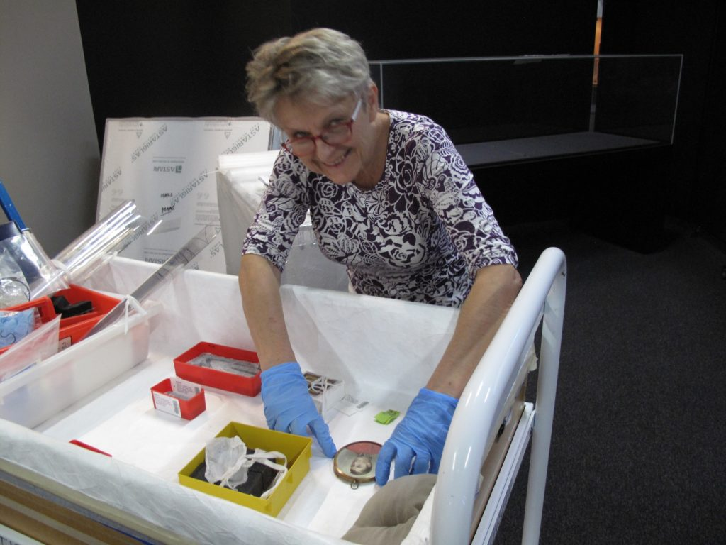 Teresa Werstak, Conservator, preparing to install a portrait miniature of Governor Lachlan Macquarie and a daguerreotype in a showcase for the Australian Men's Style display