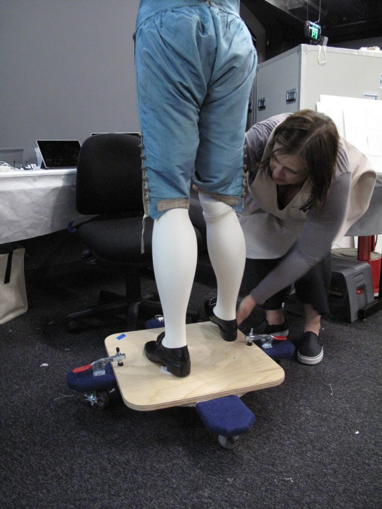 Melinda Kerstein connecting the right leg to an 18th century mannequin