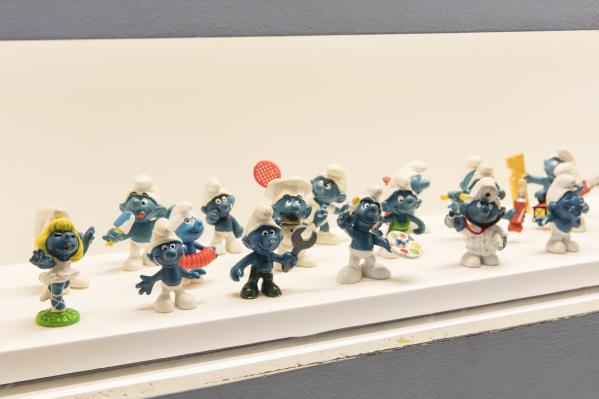 Photograph of Seventeen Smurf figurines on display