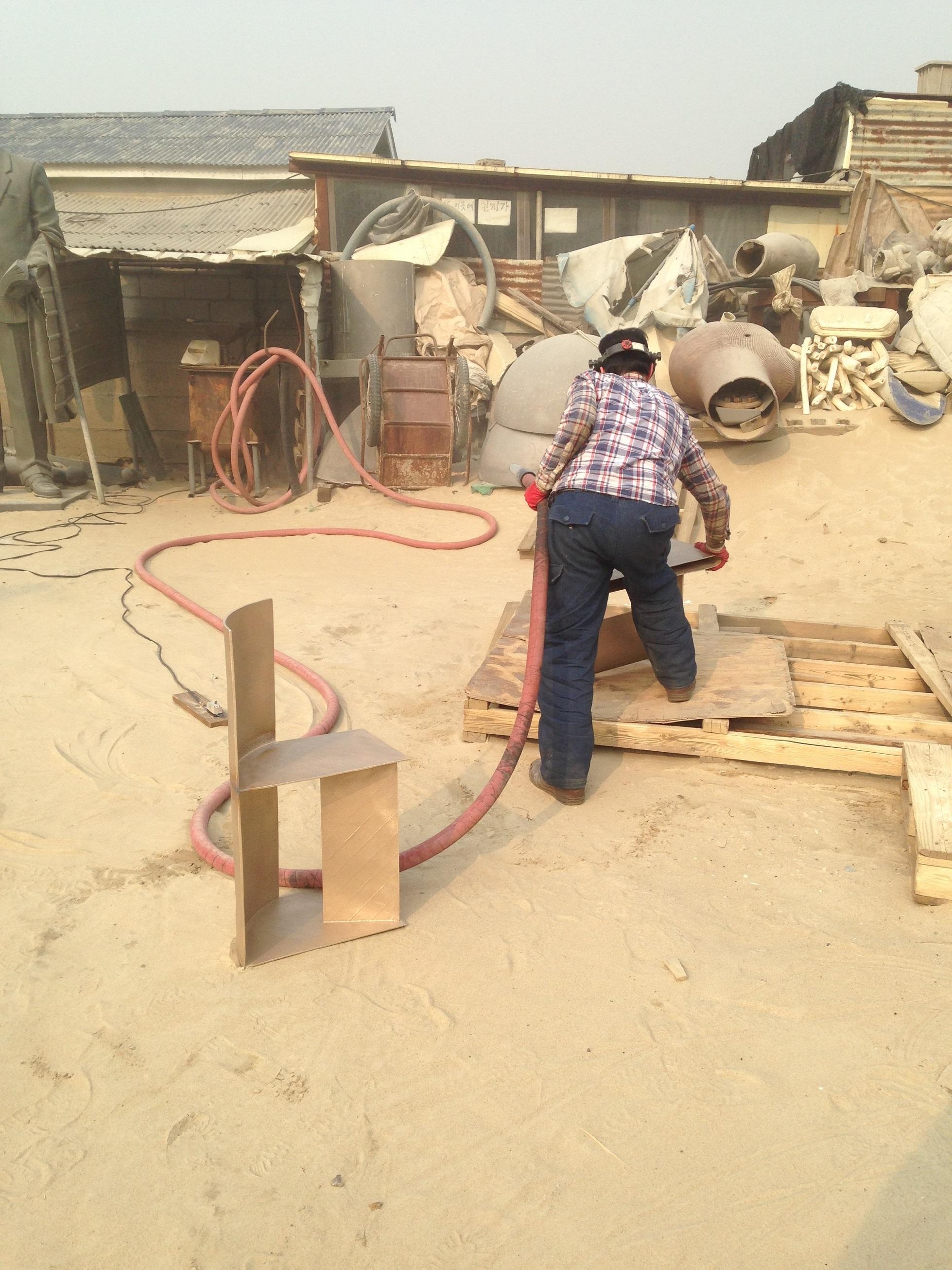 Man welding a bronze chair