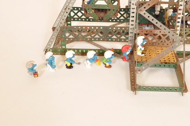 Photograph of Seven Smurf figurines in a line for a metal model ferris wheel
