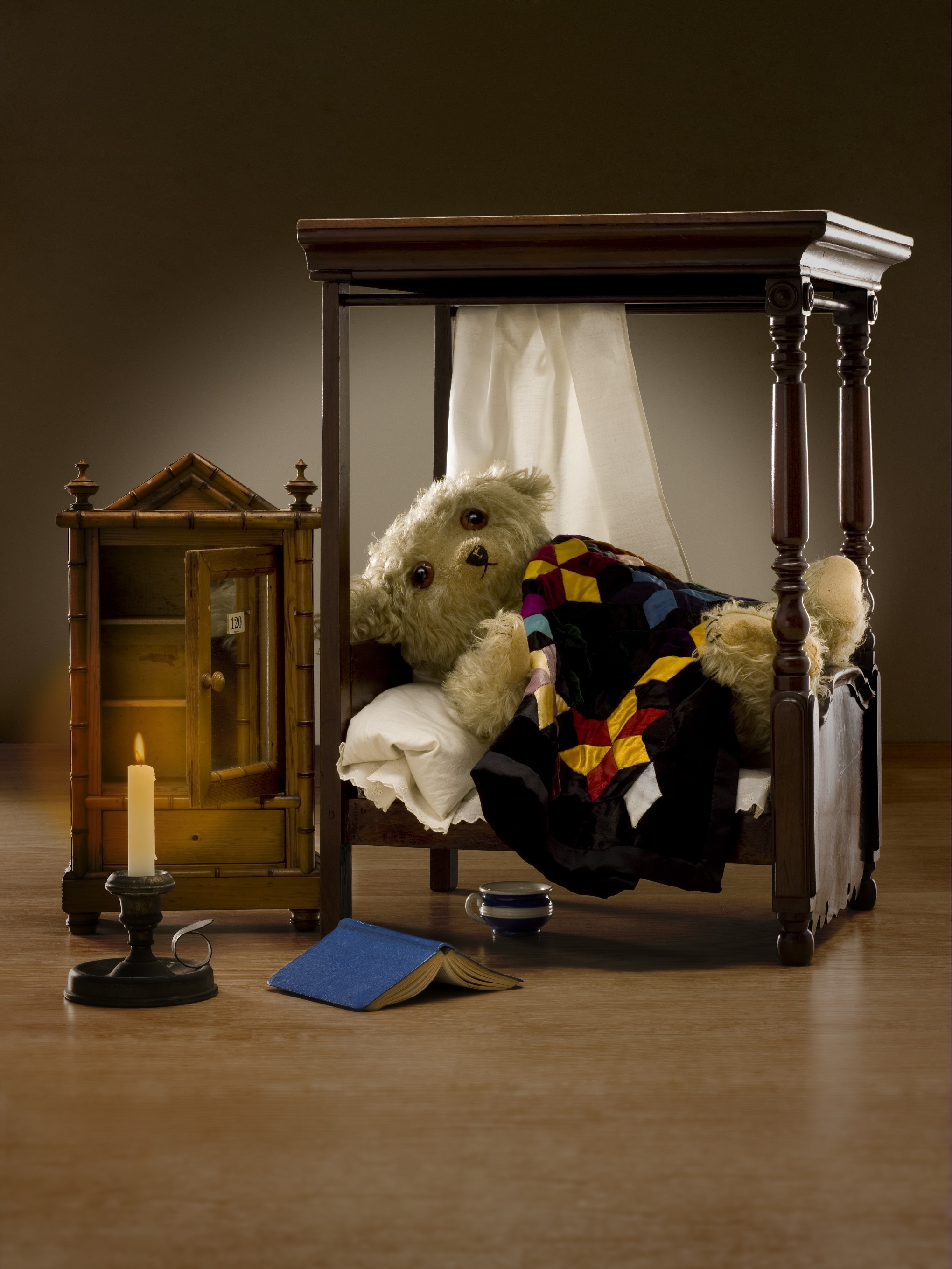 A bedroom scene with a doll's four-poster bed with a teddy bear