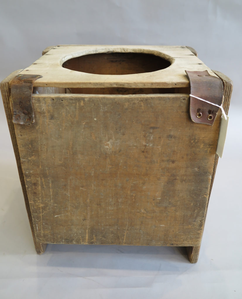 A rectangular timber box with a circular hole cut out of the top with a hinged lid to cover the hole when not in use.