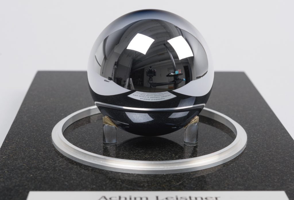 Perfectly round silver sphere held by small plastic feet.
